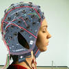A woman wearing a wired contraption for a brain computer interface